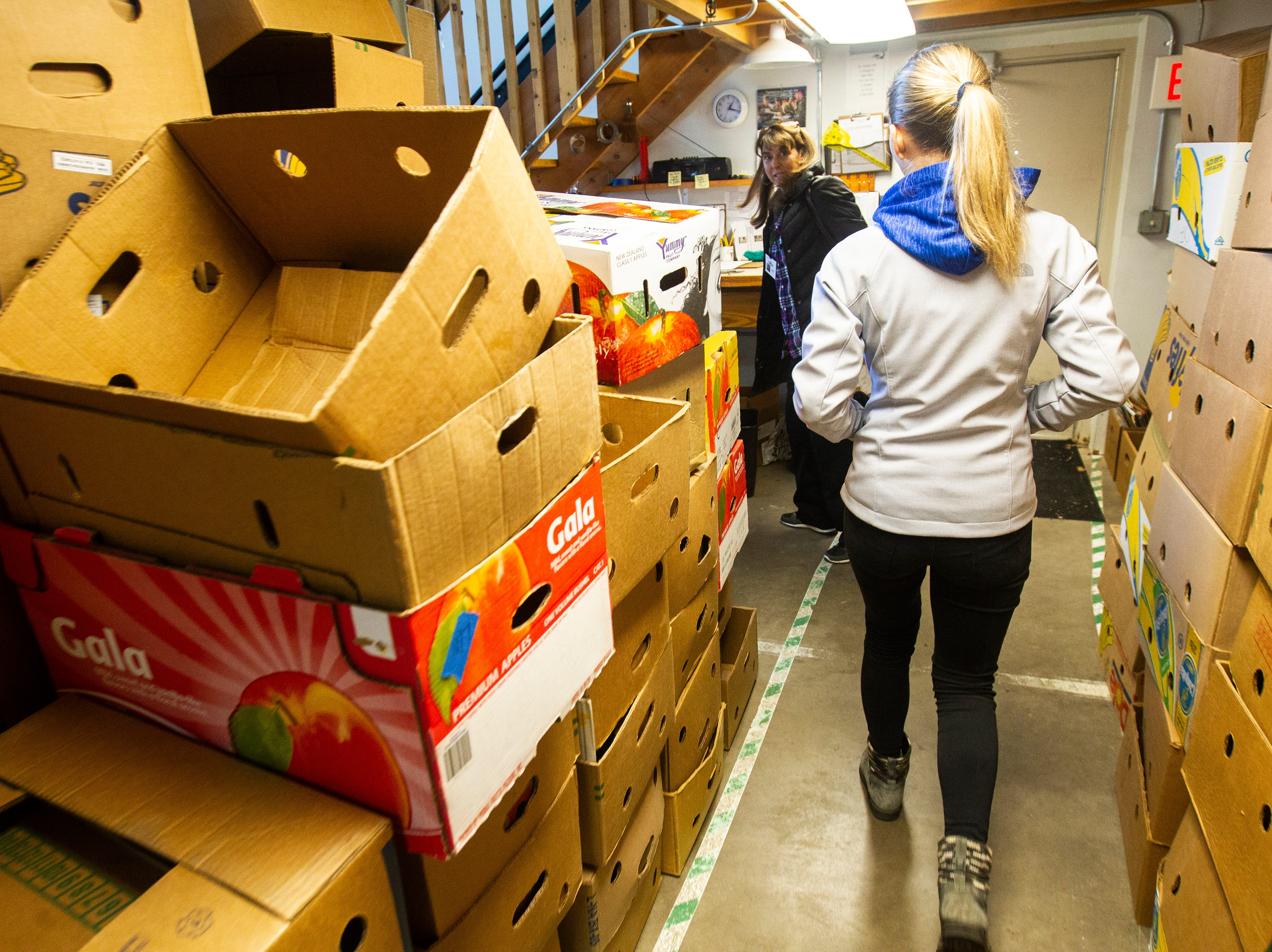 Table to Table volunteers Tatum Nass, right, and Lisa Dutchik walk through a back room filled with cardboard boxes before heading out on their afternoon route on Thursday, Nov. 15, 2018, at the Table to Table offices in Iowa City. Nass is a University of Iowa freshman studying biology and Dutchik is a lecturer in the Tippie College of Business.