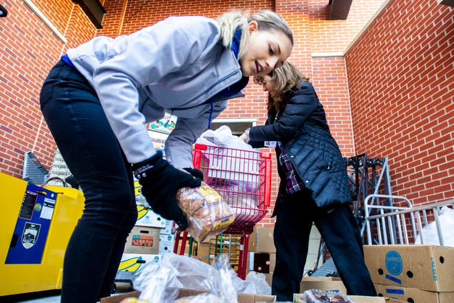 Table to Table volunteers Tatum Nass, left, and Lisa Dutchik load produce and baked goods on their afternoon route on Thursday, Nov. 15, 2018, in Coralville. Nass is a University of Iowa freshman studying biology and Dutchik is a lecturer in the Tippie College of Business.