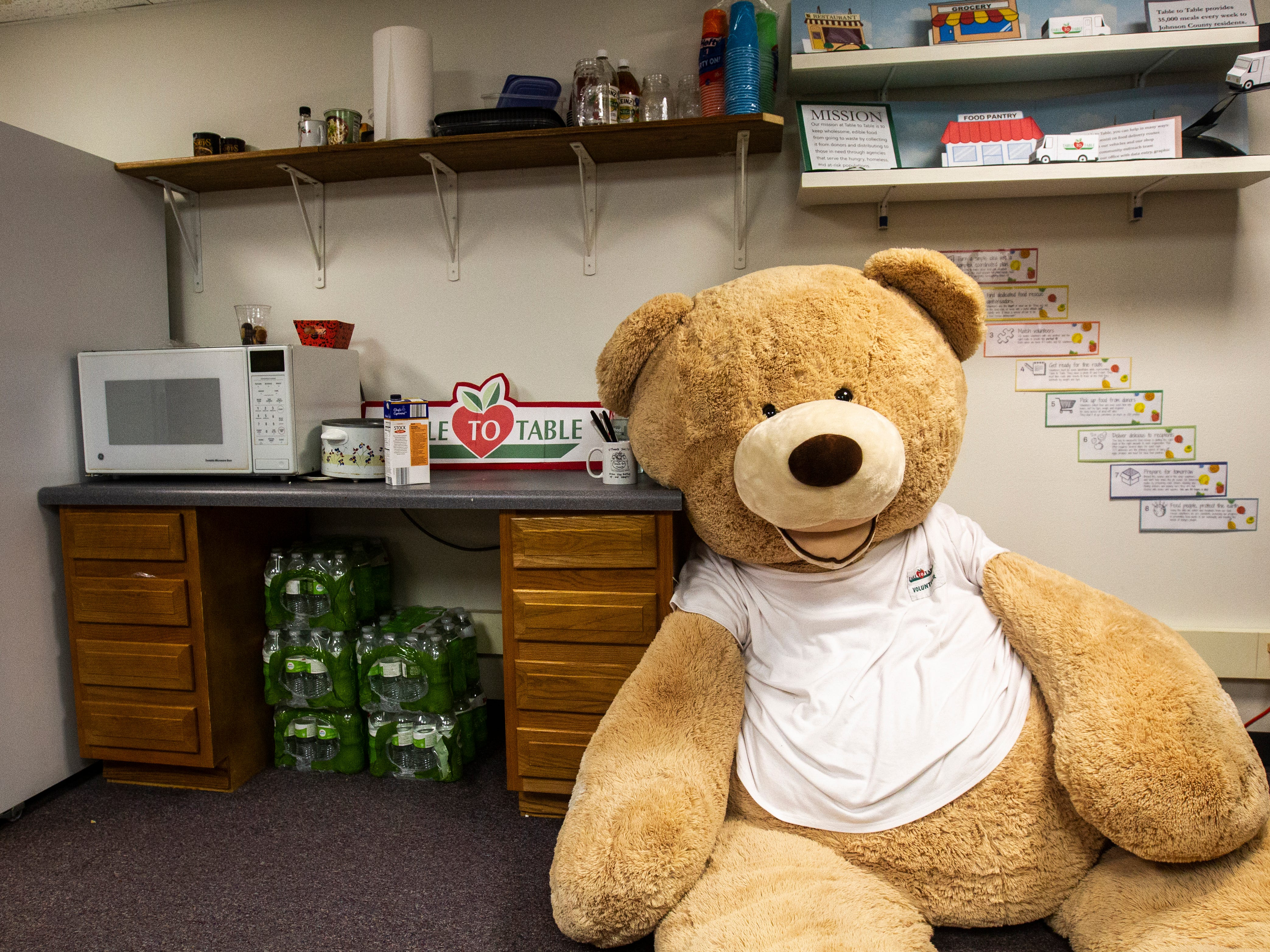 Howard, a large stuffed animal, sits in a back room while wearing a Table to Table volunteer t-shirt on Thursday, Nov. 15, 2018, at the Table to Table offices in Iowa City.