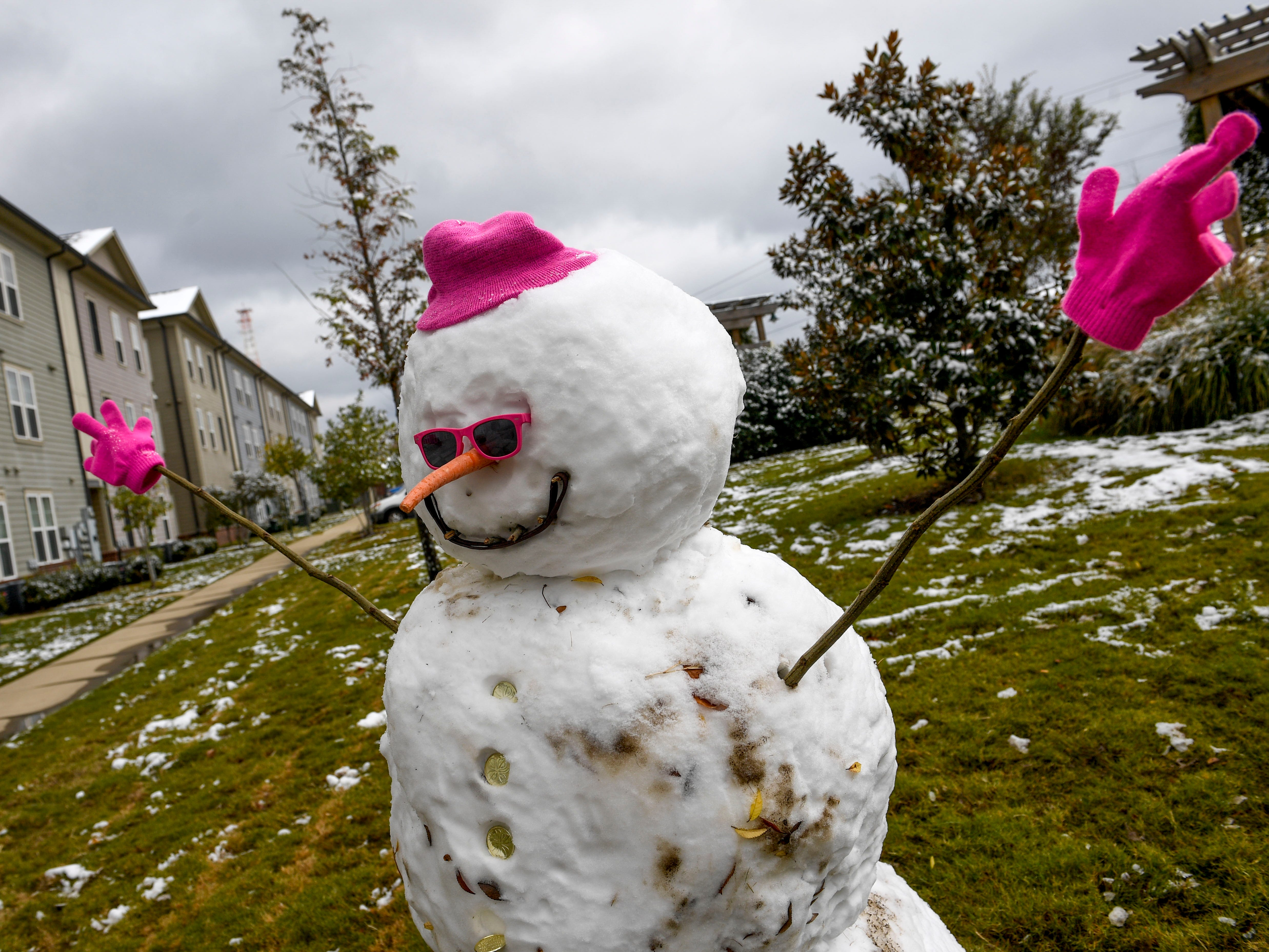 A snowman can be seen after an early snowfall coated scenes of late changing fall leaves, streets, and downtown with powdery snow in Jackson, Tenn., on Thursday, Nov. 15, 2018.