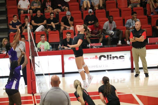 Christa Karns jumps to spike the ball over the net as coach Darrin McClure looks on during a home match this past season.