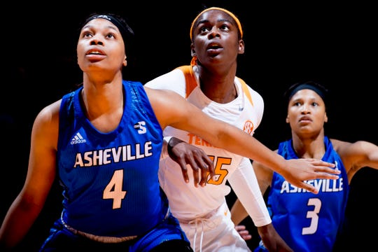 Tennessee forward Cheridene Green (15) and UNC Asheville  center Evonne McGill (4) and UNC Asheville  guard Zip Scott (3) eye the rebound during a game between Tennessee and UNC Asheville at Thompson-Boling Arena in Knoxville, Tennessee on Wednesday, November 14, 2018.