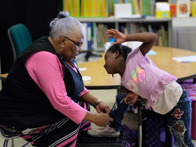 Foster Grandparent Lena Morrison helps kindergartner DeNysha Echols tie her shoe after coming in from recess at Green Magnet Academy on Wednesday, November 7, 2018 in Knoxville. Morrison has been serving as a Foster Grandparent along with her sister Hattie Crockett for three years in Knoxville.