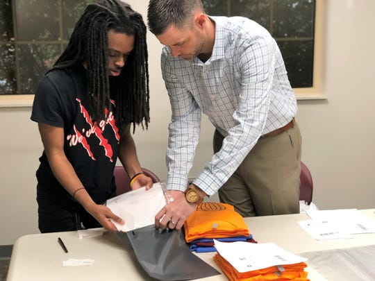Ryan Willis, right, has shown Jamal Holloway all of the steps it takes to run a business, including packaging and fulfilling orders. After the first burst of orders, Willis said that Holloway noticed some people he knew ordering t-shirts and at school his teachers and other students stop him in the halls to talk about the Positively Knox Project.