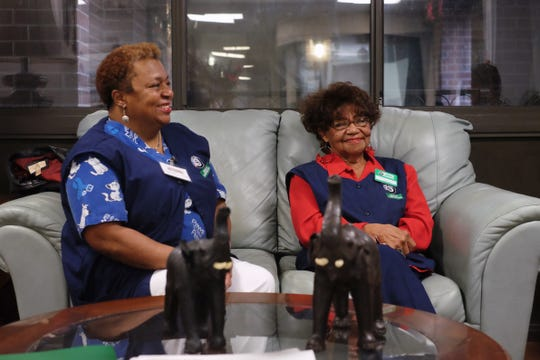 Rhonda Brooks, left, and her mother, Peggy Davis, discuss their roles in aiding senior residents at the Broadway Towers earlier this month. Davis started serving in the Senior Companion program 21 years ago, and her daughter joined the program six years ago.