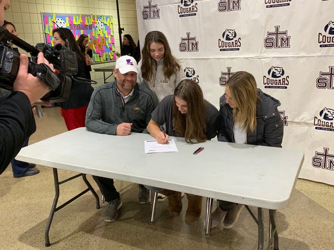St. Thomas More's Meredyth Howard signs her National Letter of Intent to play volleyball at LSU during a ceremony  Wednesday at STM.