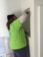 Suzi Henry paints in a soon-to-be neighbor's Habitat for Humanity home in Lafayette, Louisiana, Nov. 15, 2018.
