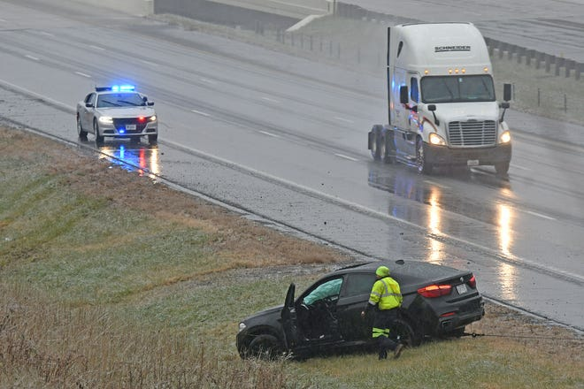 A crash in the northbound lane of Interstate 71 is cleaned up early Thursday morning. Wet and icy conditions made travel challenging for morning commuters.
