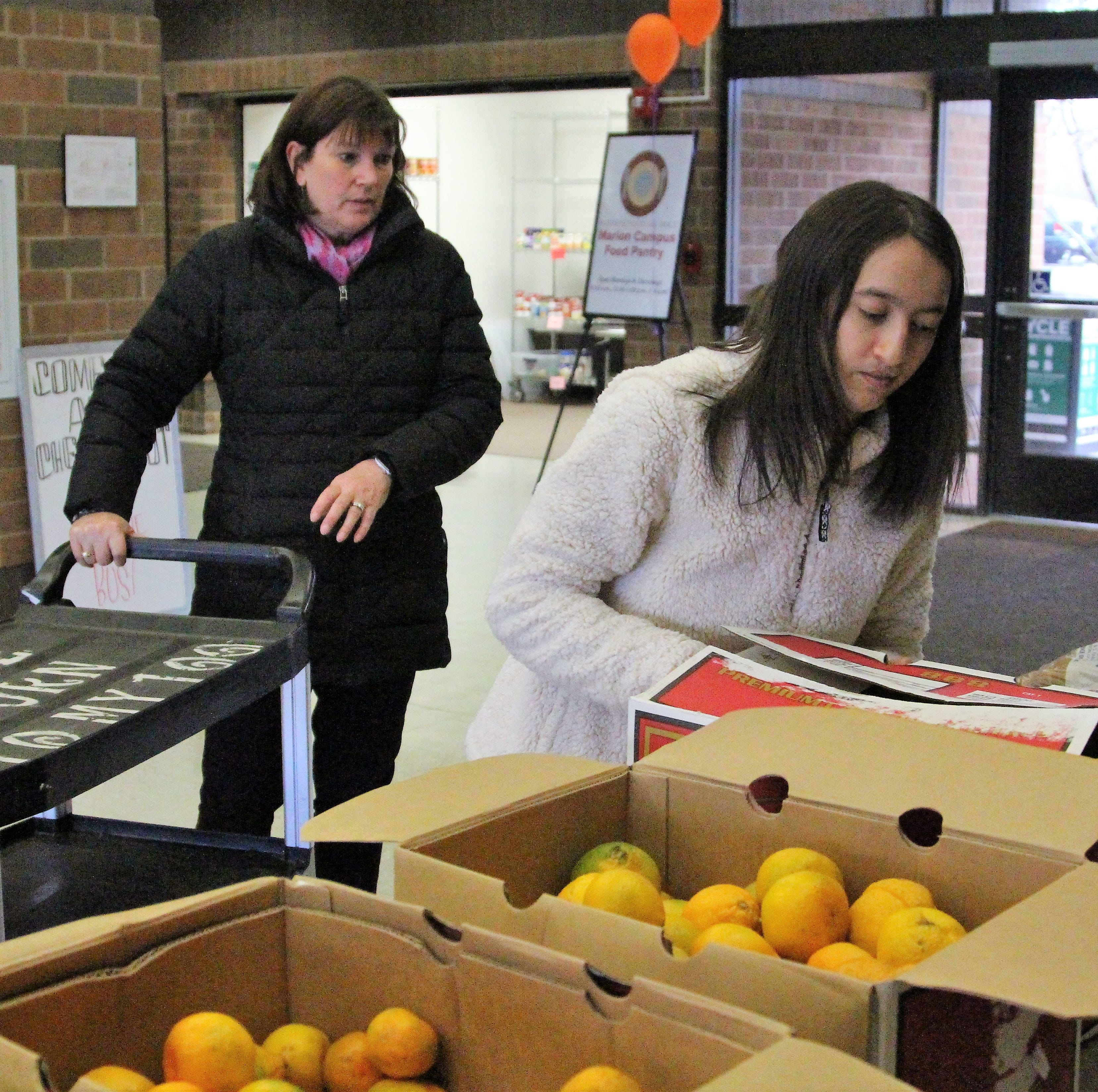 Ohio State Marion Student Paige Montgomery, 22,  sets down a box of oranges during a free produce market on Thursday. A recent study found that 26.7 percent of students surveyed at the campus dealt with food insecurity.
