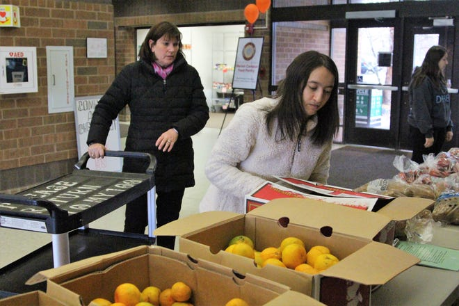 Ohio State Marion Student Paige Montgomery, 22, sets down a box of oranges during a free produce market. A recent study found that 26.7 percent of students surveyed at the campus dealt with food insecurity.