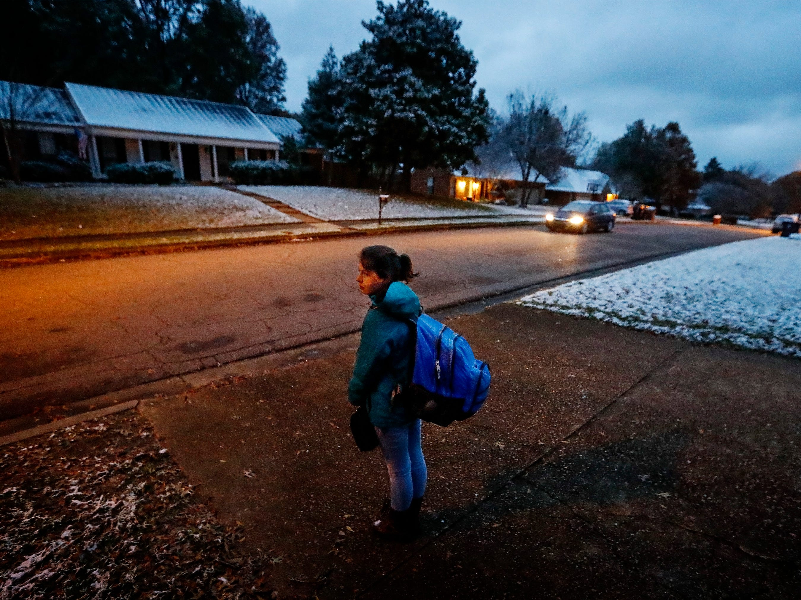 Collierville High School student Casey Hanauer,16, waits for a school bus at 6:09 a.m. in her neighborhood Thursday morning. Collierville parents want the school times to start later and the Collierville School District formed a committee to explore the possible benefits and impact the change in time would have on students.