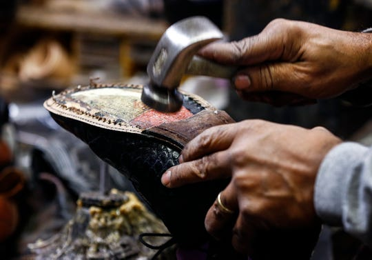 Alvin Hooper, owner of Nu-Life Shoe Repair shop on Summer replaces the sole on a pair of mens wingtip shoes.