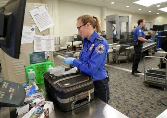 A TSA officer looks through carry-on baggage in the security screening area at Mitchell International. The TSA says it discovered 24 guns at Wisconsin airport checkpoints in 2019.