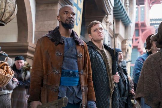 "John (Jamie Foxx, left) shows Robin (Taron Egerton) the ropes in ""Robin Hood."""
