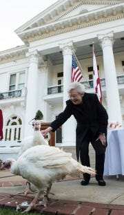 Alabama Gov. Kay Ivey pets turkeys, Henrietta and Clyde, during the annual turkey pardon outside the governor's mansion in Montgomery, Ala., on Thursday, Nov. 15, 2018.