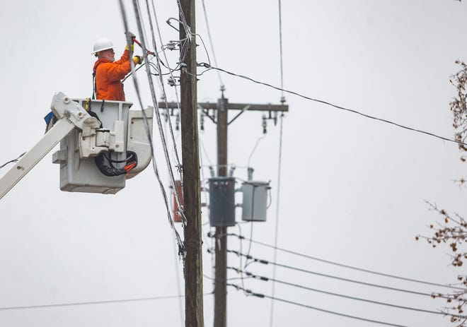 Crewmen work to restore power in Muncie after Thursday's ice storm.