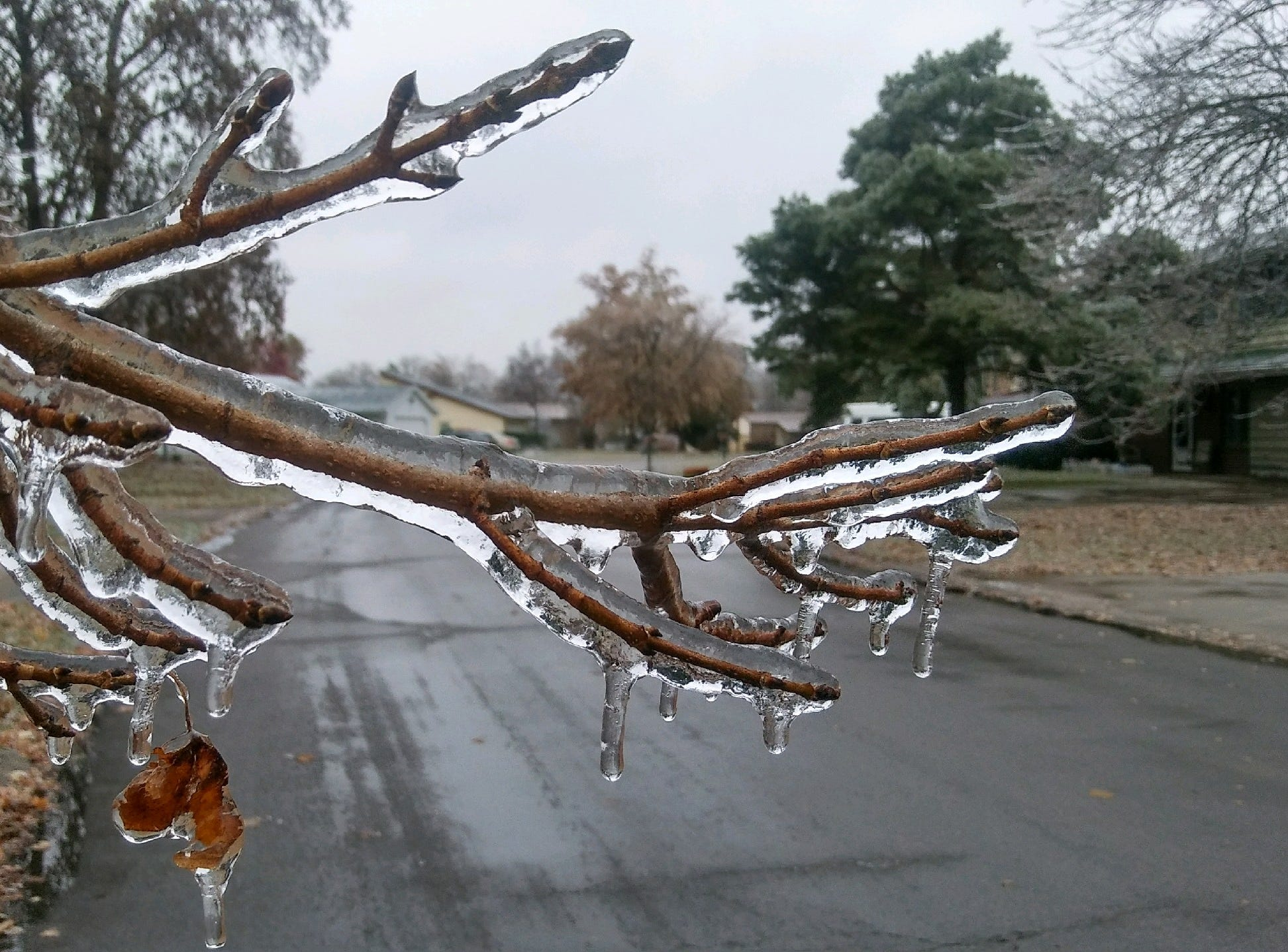 Ice from overnight sleet blankets road signs and more causing travel advisories, school cancellations and even power outages.