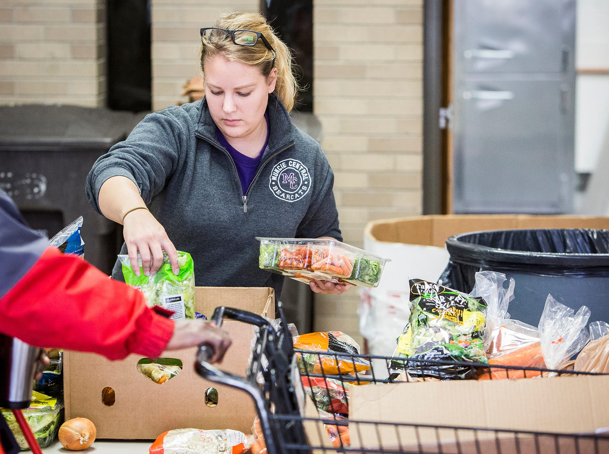 Volunteers work with recipients during Second Harvest's school food pantry program after school at Central.