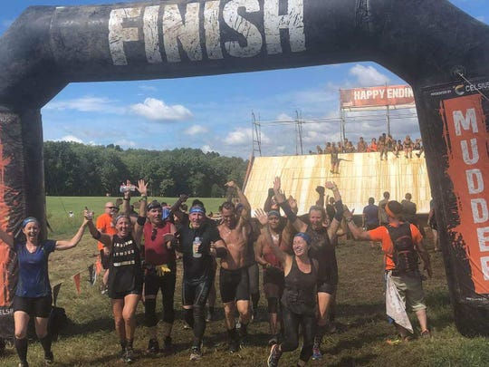 Bruce Ippel of Smyrna, center, gets across the finish line of a Tough Mudder competition with a little help from friends.