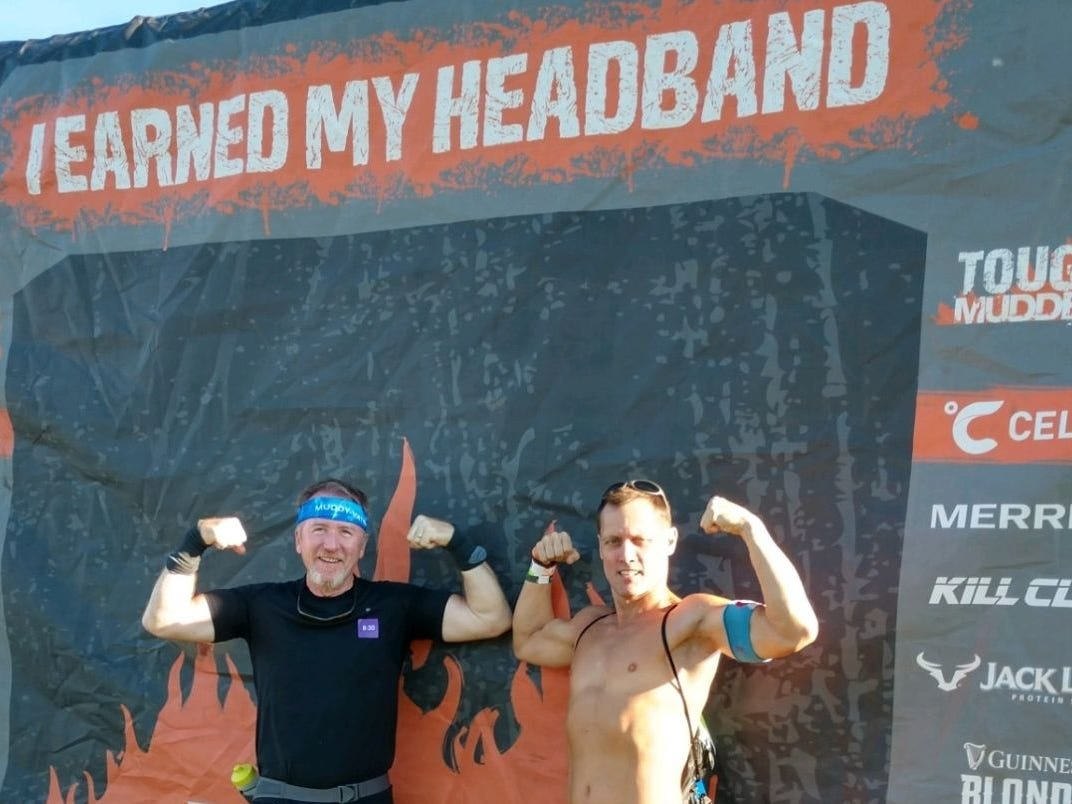Bruce Ippel of Smyrna, left, poses with his coach, Roger Brady, after the two made it across the finish line of a Tough Mudder competition.
