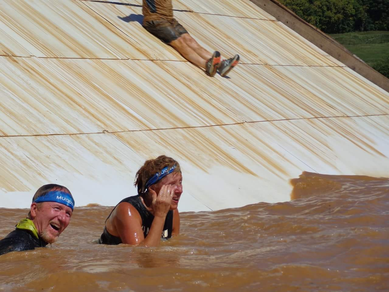 Bruce Ippel and a fellow Tough Mudder competitor enjoy a dip in muddy water during the summertime competition.