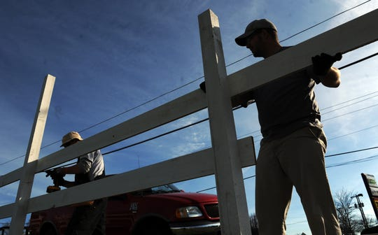 City of Franklin employees Tim Beard, left, and Ryan Kelley help install a new fence along Franklin Road in front of the Park at Harlinsdale Farm.