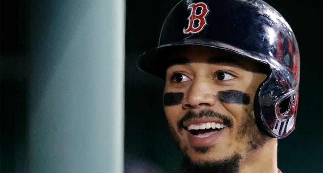 Boston Red Sox's Mookie Betts smiling after scoring on a single by Xander Bogaerts against the Baltimore Orioles on Sept. 24, 2018.