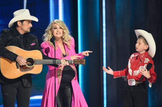 Hosts Brad Paisley and Carrie Underwood interact with Mason Ramsey during the opening set at the 52nd Annual CMA Awards at Bridgestone Arena Wednesday Nov. 14, 2018, in Nashville, Tenn.