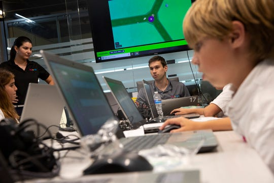 Class instructor Conner Burgess, center, talks with his students during a coding class Wednesday, Nov. 14, 2018, at Logiscool in Naples.