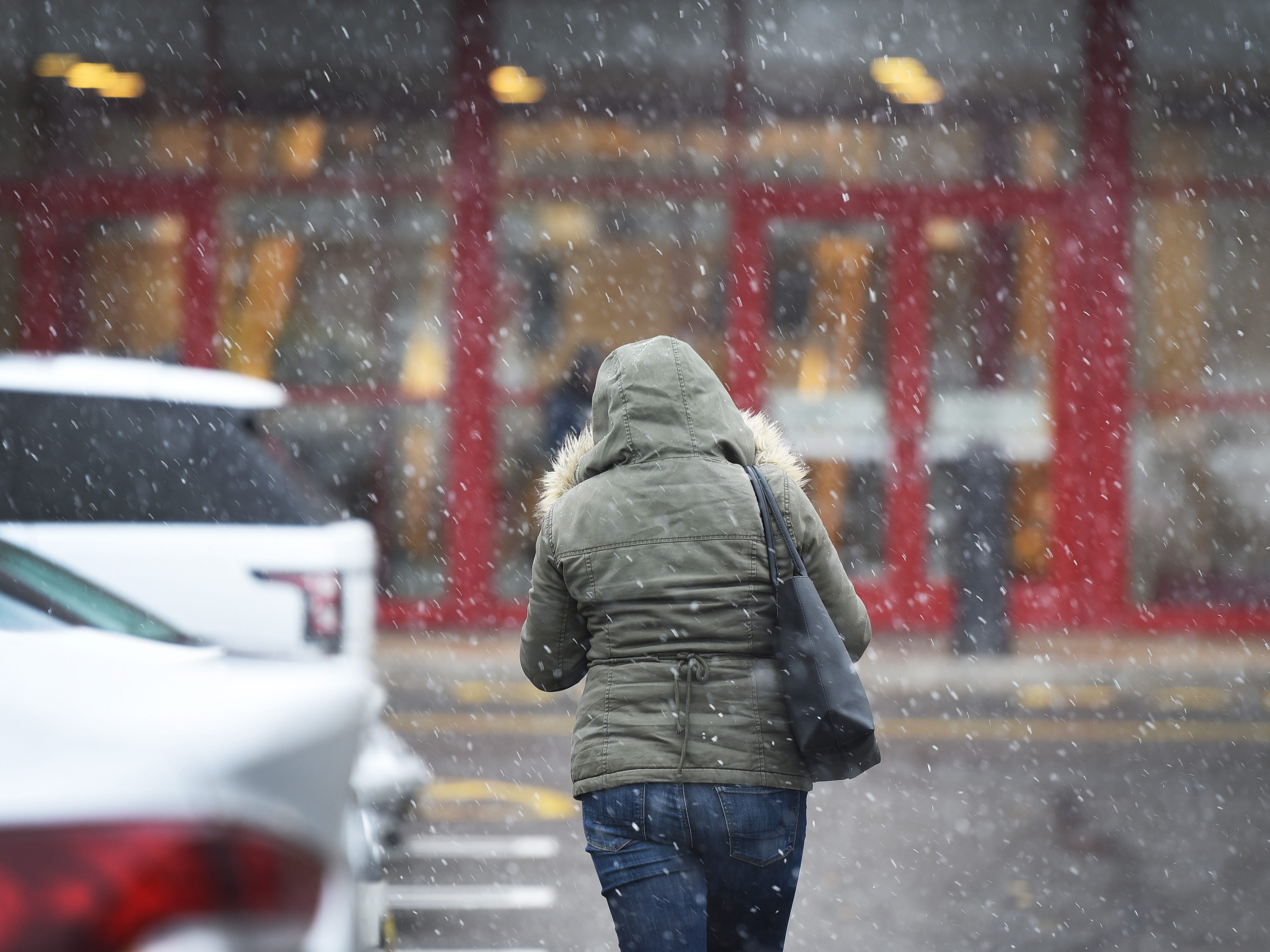 November 15, 2018, Paramus, NJ, USAA shopper shield herself from the snow as the snow begins to fall at Bergen Town Center.