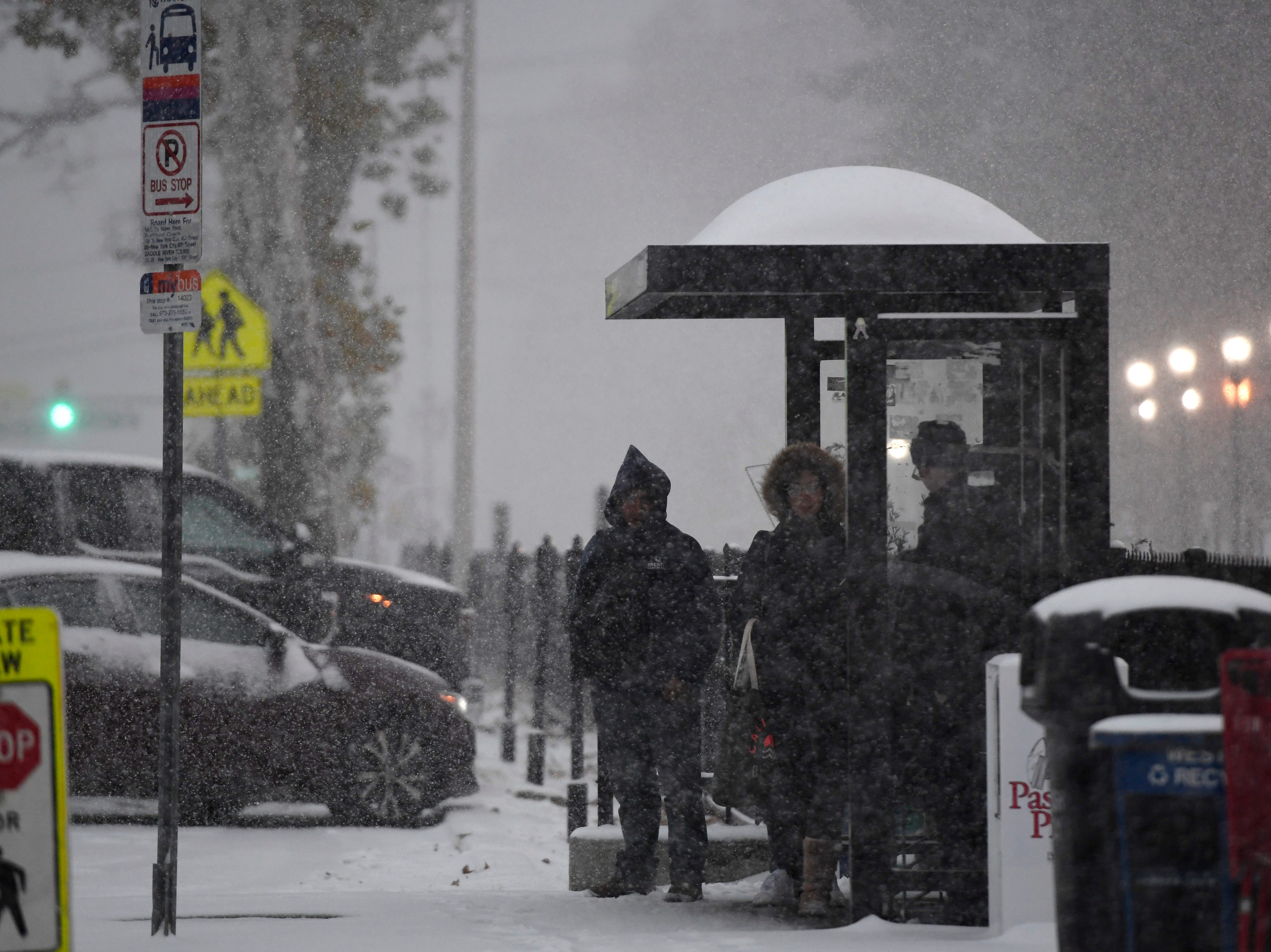 People wait for a NJTransit bus at the Broadway stop as the first snowfall of the year hits North Jersey on Thursday, Nov. 15, 2018, in Westwood.