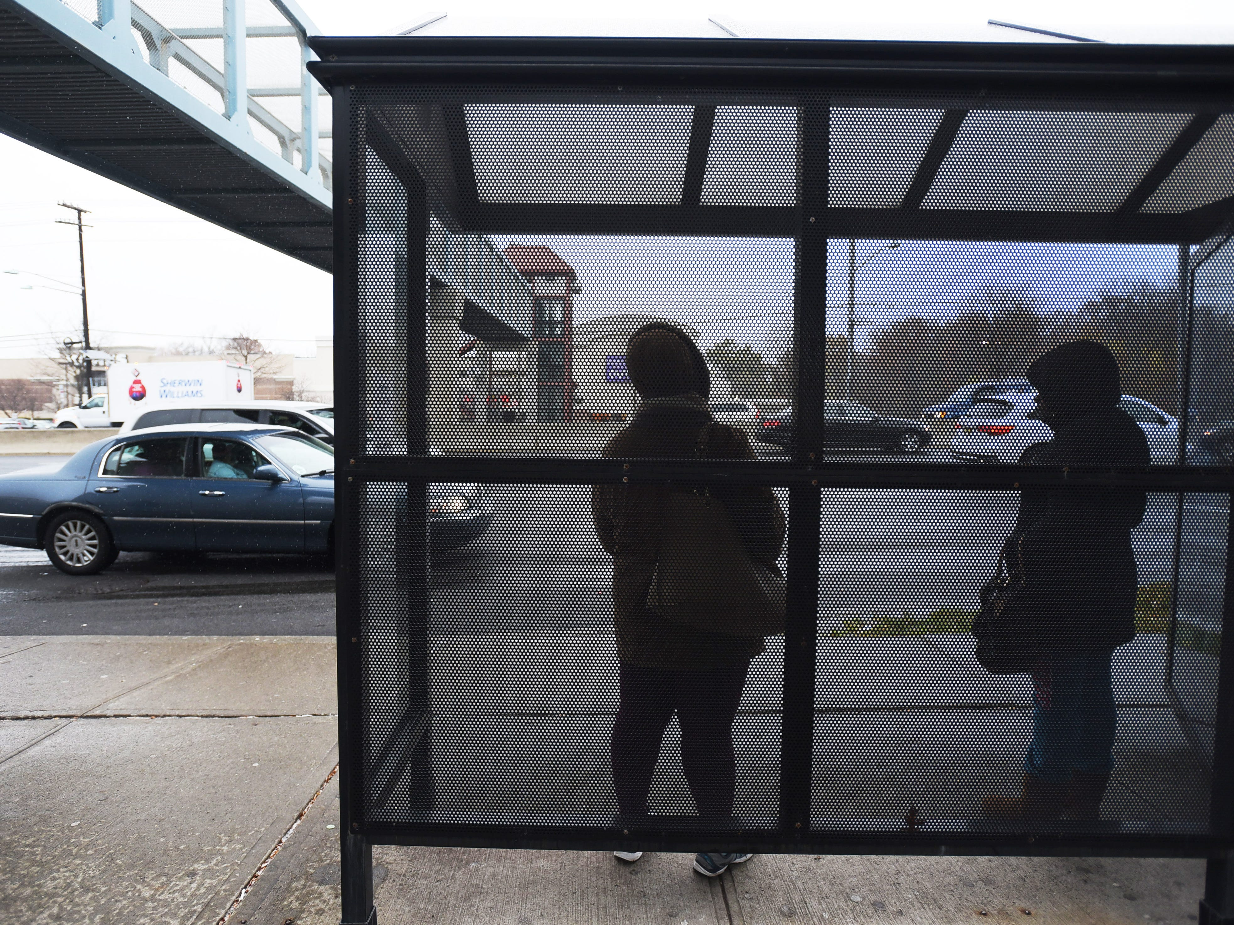 November 15, 2018, Paramus, NJ, USAPeople wait at a bus stop along Route 4 East as the snow begins to fall at Bergen Town Center.