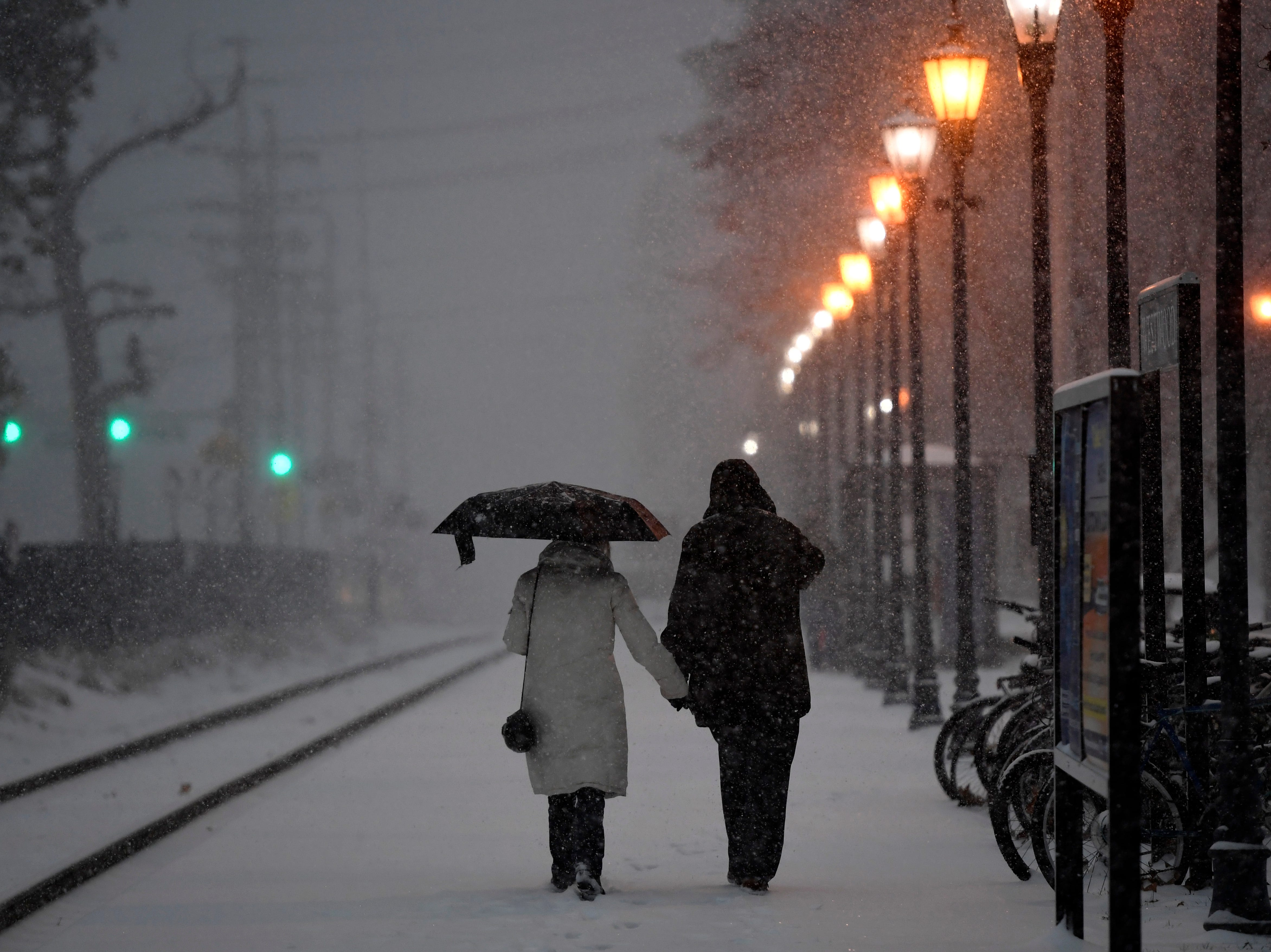 A couple walks along the railroad tracks into the Westwood NJ Transit train station as snow falls on Thursday, Nov. 15, 2018, in Westwood.