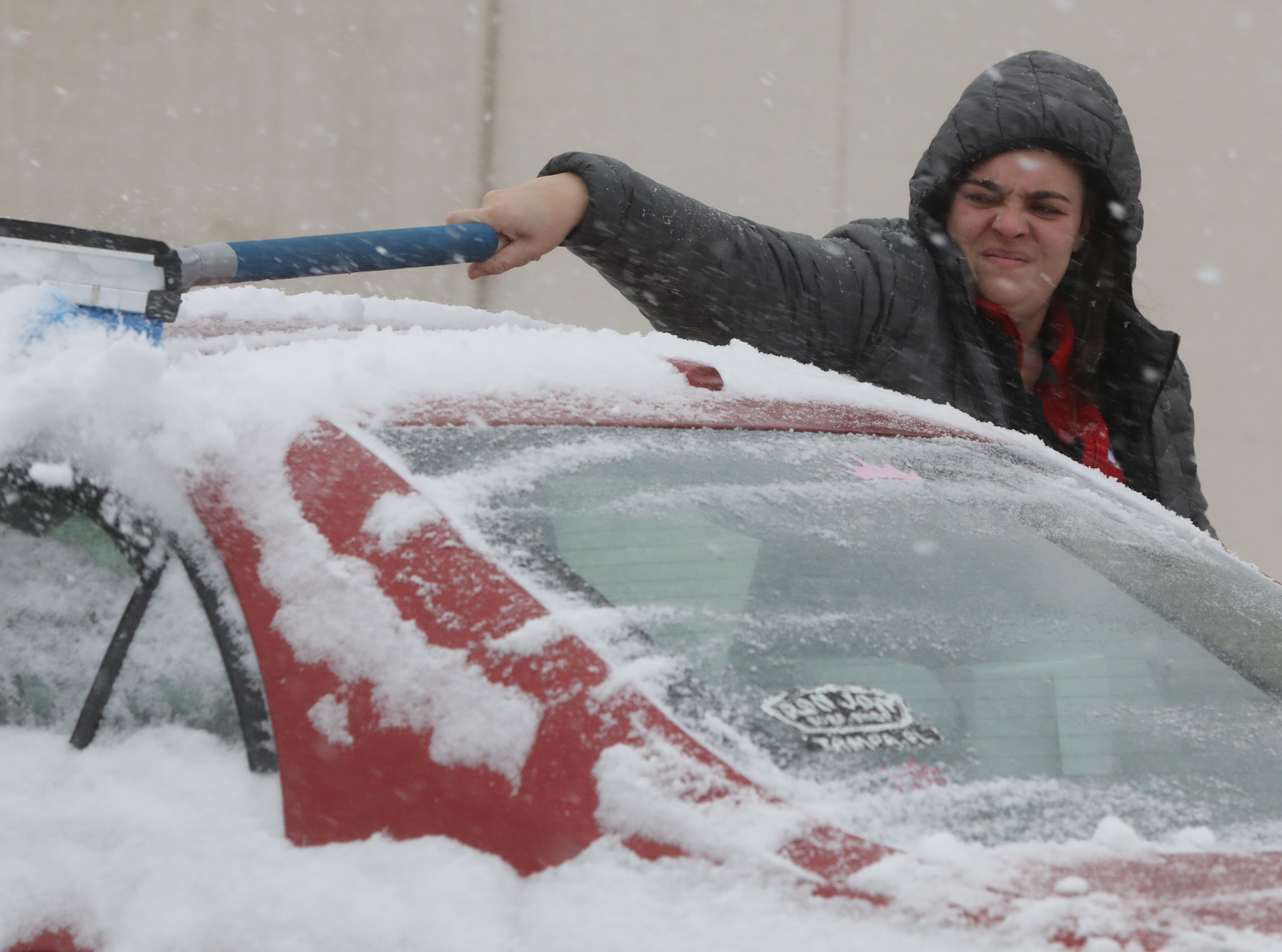 Kassie Mattoon of Woodland Park clears snow from her car as she heads home after working this afternoon at Applebees in Totowa.