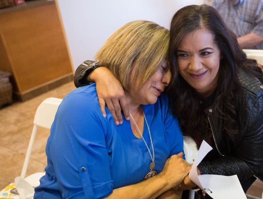 Bertha Granillo, right, hugs Cande Laney, left, as Laney found out she was the winner of a contest to award a $50,000, full-arch restoration treatment from Oral and Facial Surgery of New Mexico, Thursday, Nov. 15, 2018.