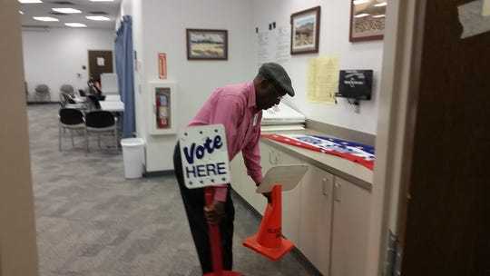 "Poll worker Lawrence Kenniebrew takes in the ""vote here"" signs at Thomas Branigan Memorial Library on election night, Tuesday, Nov. 6, 2018 after the close of the polling site."