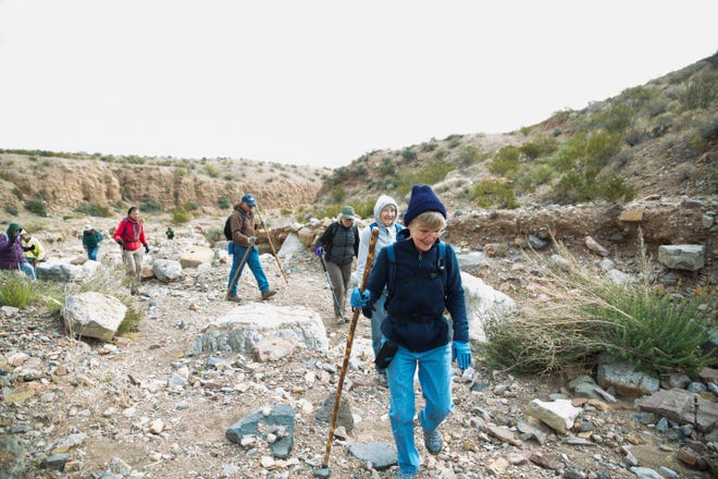 Sue Spence, center, hikes a trail at Prehistoric Trackways National Monument with a group of hikers.