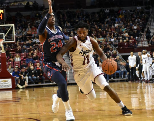 New Mexico State's C.J. Bobbitt brings the ball down the middle of the key against a Saint Mary's defender on Wednesday night at the Pan American Center.