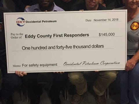 Members of Occidental Petroleum and Eddy County emergency officials hold a check that is set to help law and fire personnel across the county.