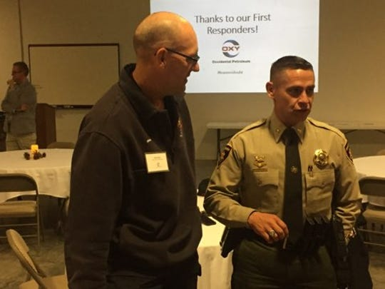 (From left)-Travis Olbert, deputy director of Eddy County Fire Services and Capt. Arsenio Jones of the Eddy County Sheriff's Office talk about emergency services during a dinner Nov. 14, 2018.