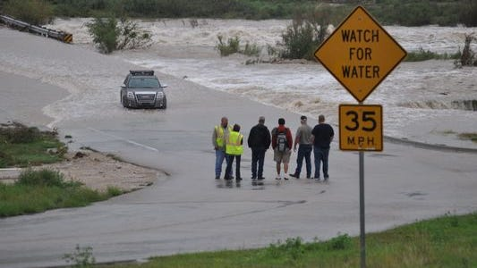 A man consults with officials on how to retrieve his vehicle, which he drove into flood waters from the Pecos River on Callaway Drive in 2014.