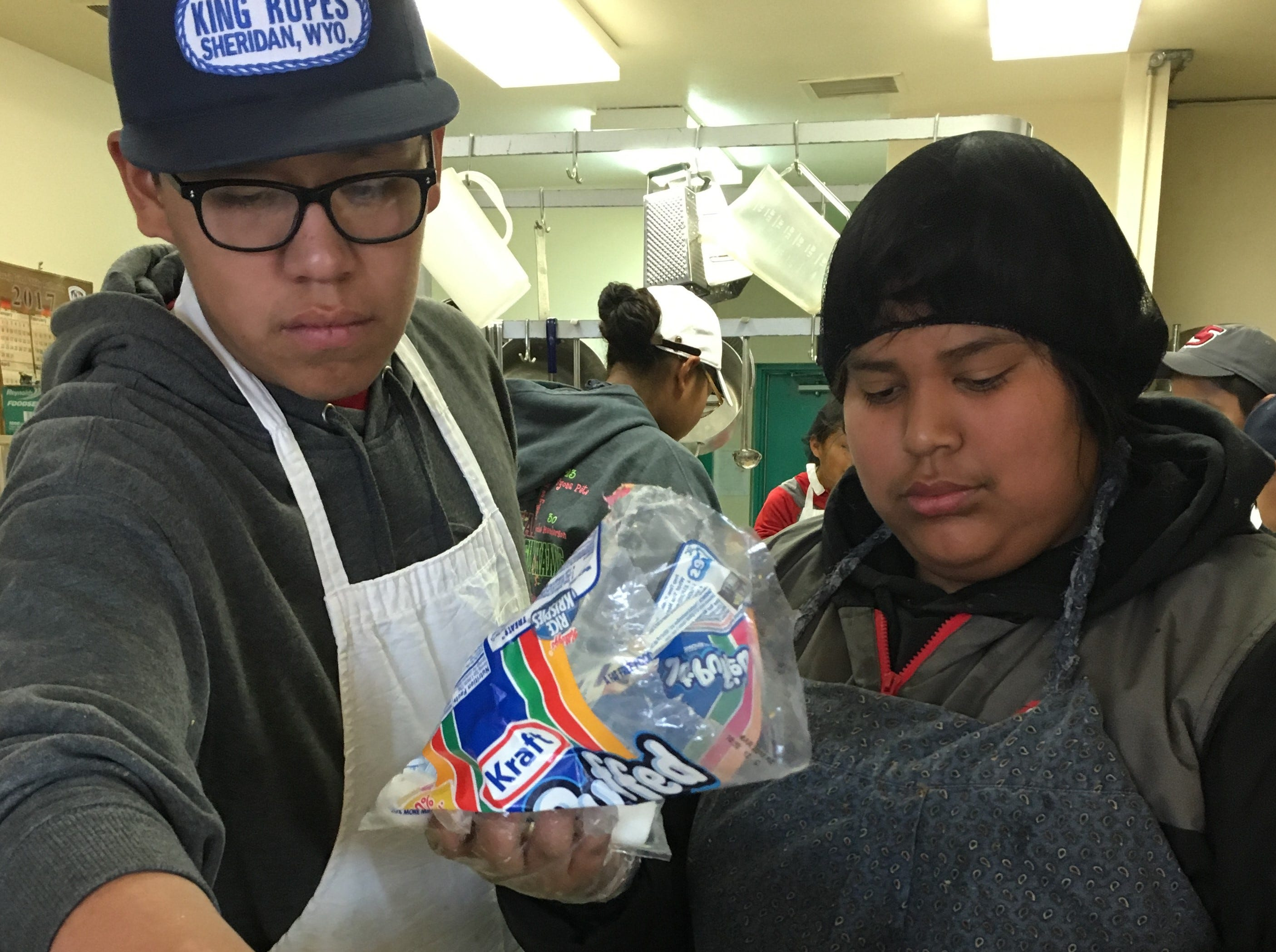 Eighth-graders Jaylon Begay, left, and Dominic Lomelin top a tray of yams with marshmallows on Wednesday at the Shiprock Senior Citizen Center in Shiprock.