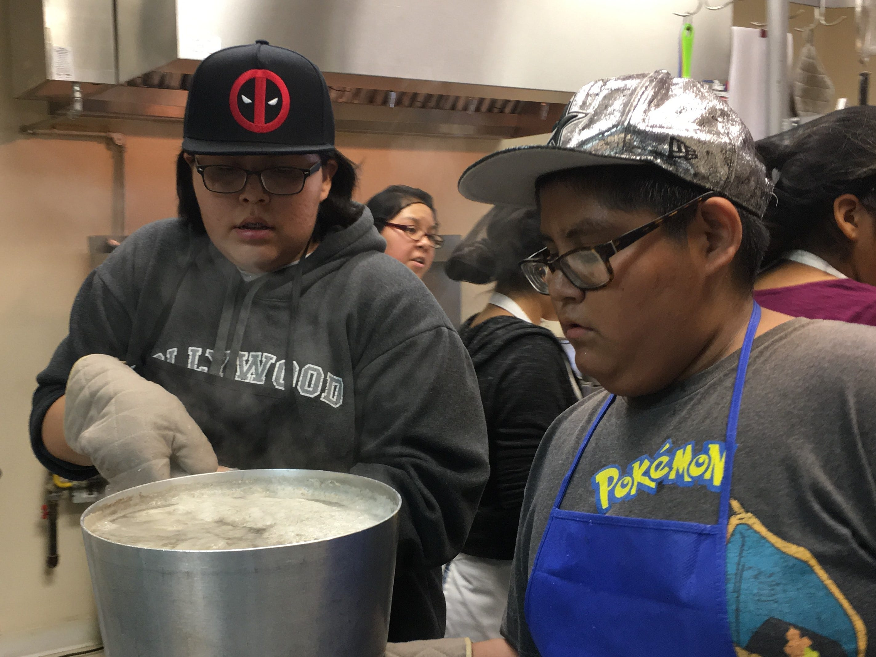 Eighth-grader Felicia Allan, left, and seventh-grader Nathaniel Bahe carry a pot of boiled potatoes on Wednesday at the Shiprock Senior Citizen Center in Shiprock.