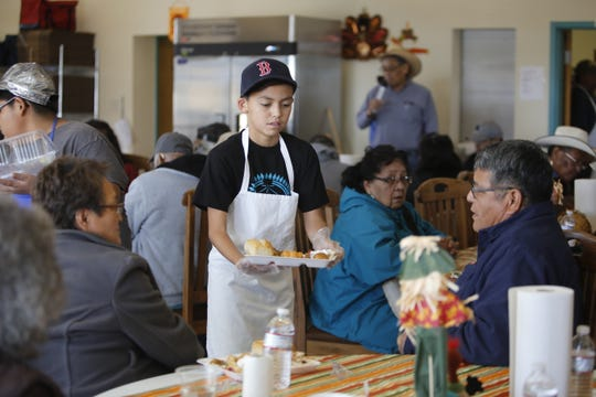 Tsé Bit A'í Middle School seventh-grader Jude Thomas delivers a tray of food during a Thanksgiving dinner on Wednesday at the Shiprock Senior Citizen Center in Shiprock.