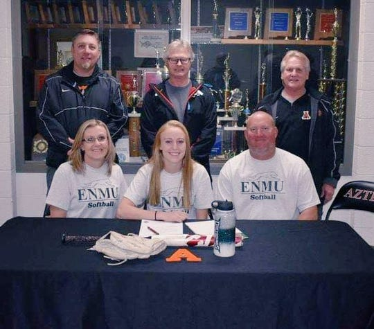 Aztec's Alanna Larkins signs her letter of intent on Wednesday to continue her softball career at Eastern New Mexico University.