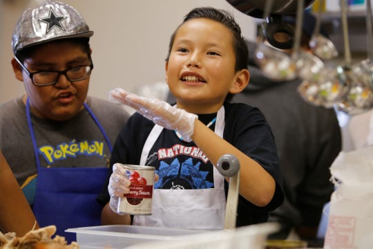Seventh-grader Nevaughn Begay tries to remove cranberry sauce for a side dish he was fixing for a Thanksgiving dinner on Wednesday at the Shiprock Senior Citizen Center in Shiprock.