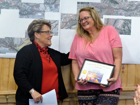 Kathy Richardson, at right, office manager at the Forestry Department, receives her plaque from Village Manager Debi Lee.