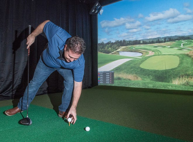There are two golf simulators for customers. Dave Peterson sets his golf ball on a tee.