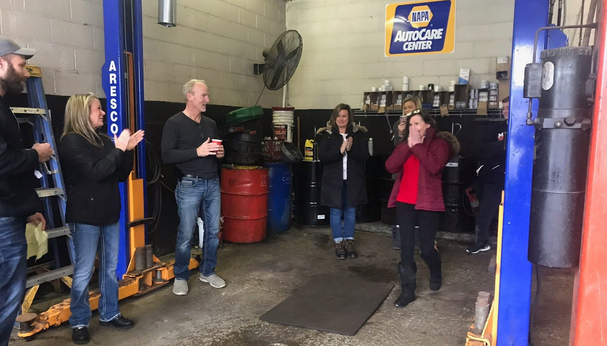 Milford resident Tammy Stockbridge (far left) reacts to being given a car through a program sponsored by local businesses.