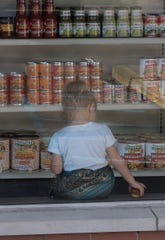 As seen through the front window of the market, 3-year-old Penelope Penaloza plays inside her mom and dad's new store.